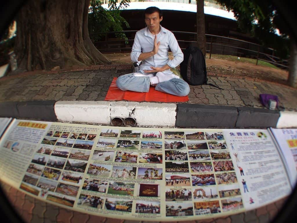 Falun Gong, Malaysia man sitting in meditation with photos