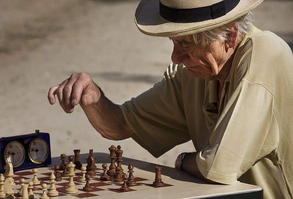 old man playing chess in a park