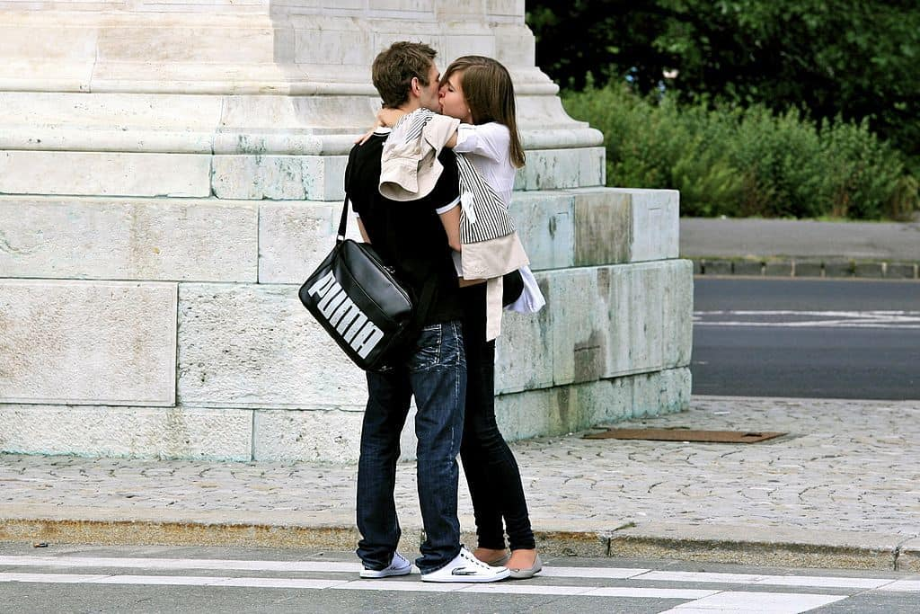 Young couple kissing on street in stylish clothes - The happiness challenge