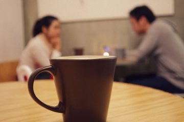 A young man and woman have a quiet conversation with a coffee cup in the foreground - Myers-Briggs humour