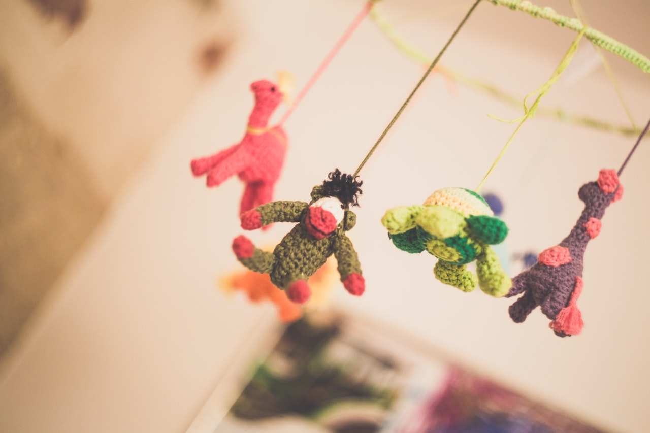 Colourful baby mobile hanging over crib - I'm a soul and I'm perfect
