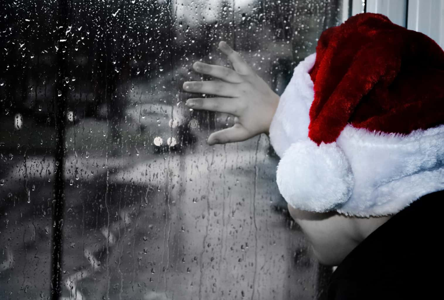 Person looking out rainy window while wearing Santa hat - Poems by Mike Larcombe