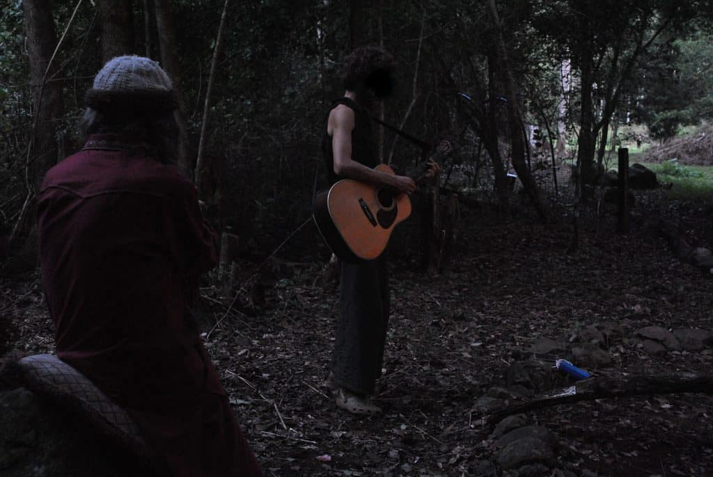 man playing guitar in woods