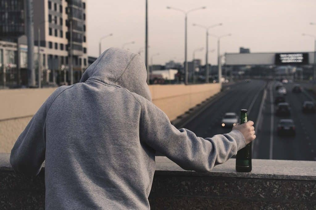 man on bridge with bottle of beer in hand