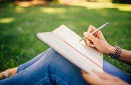Woman writing outdoors in notebook - Circadian