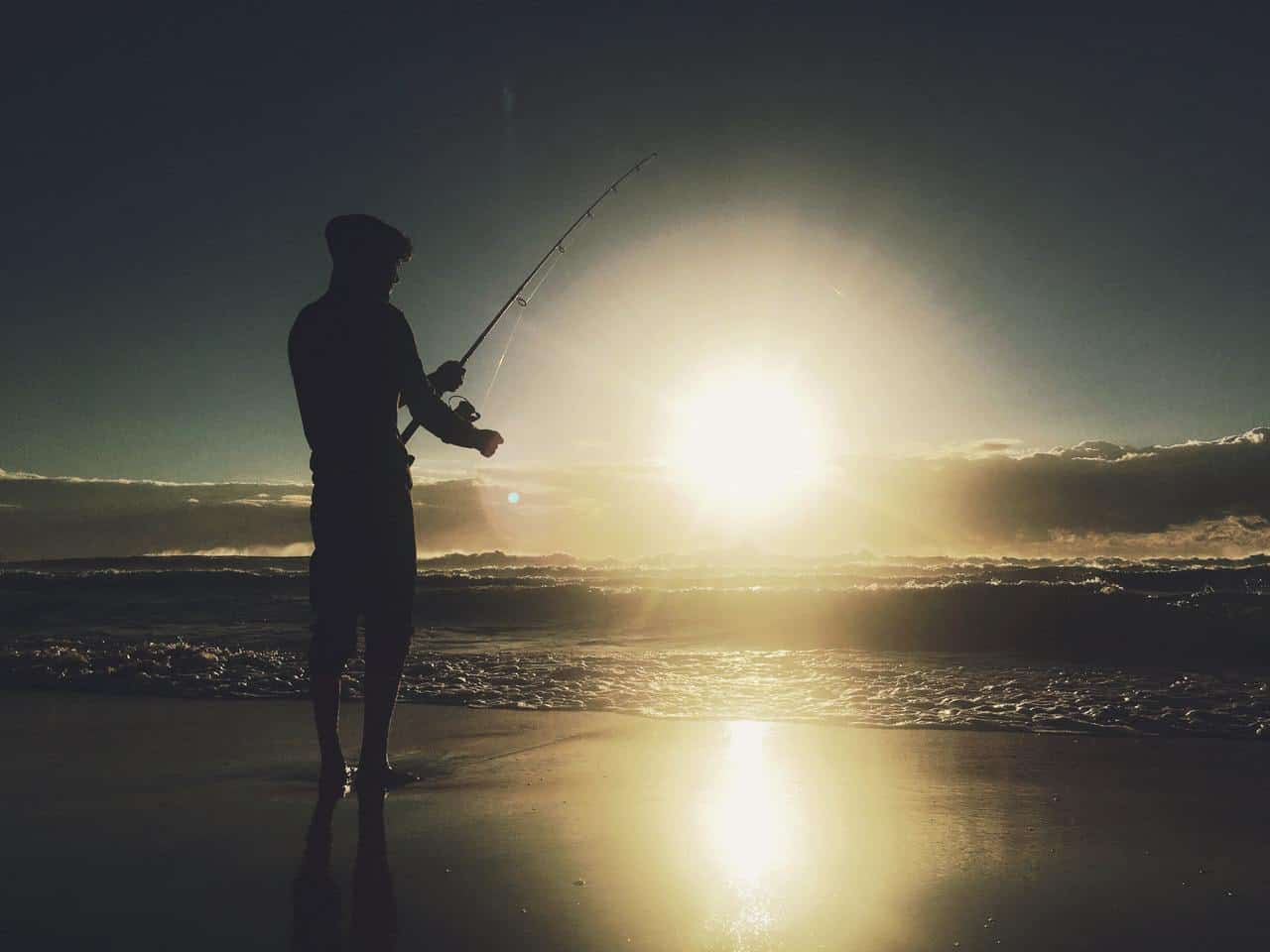 Man fishing on sandy beach with glare of white light in front of him - Inquire deeply