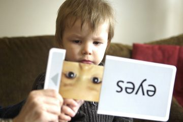 Young boy on autistic spectrum works with flash cards - A is for autism