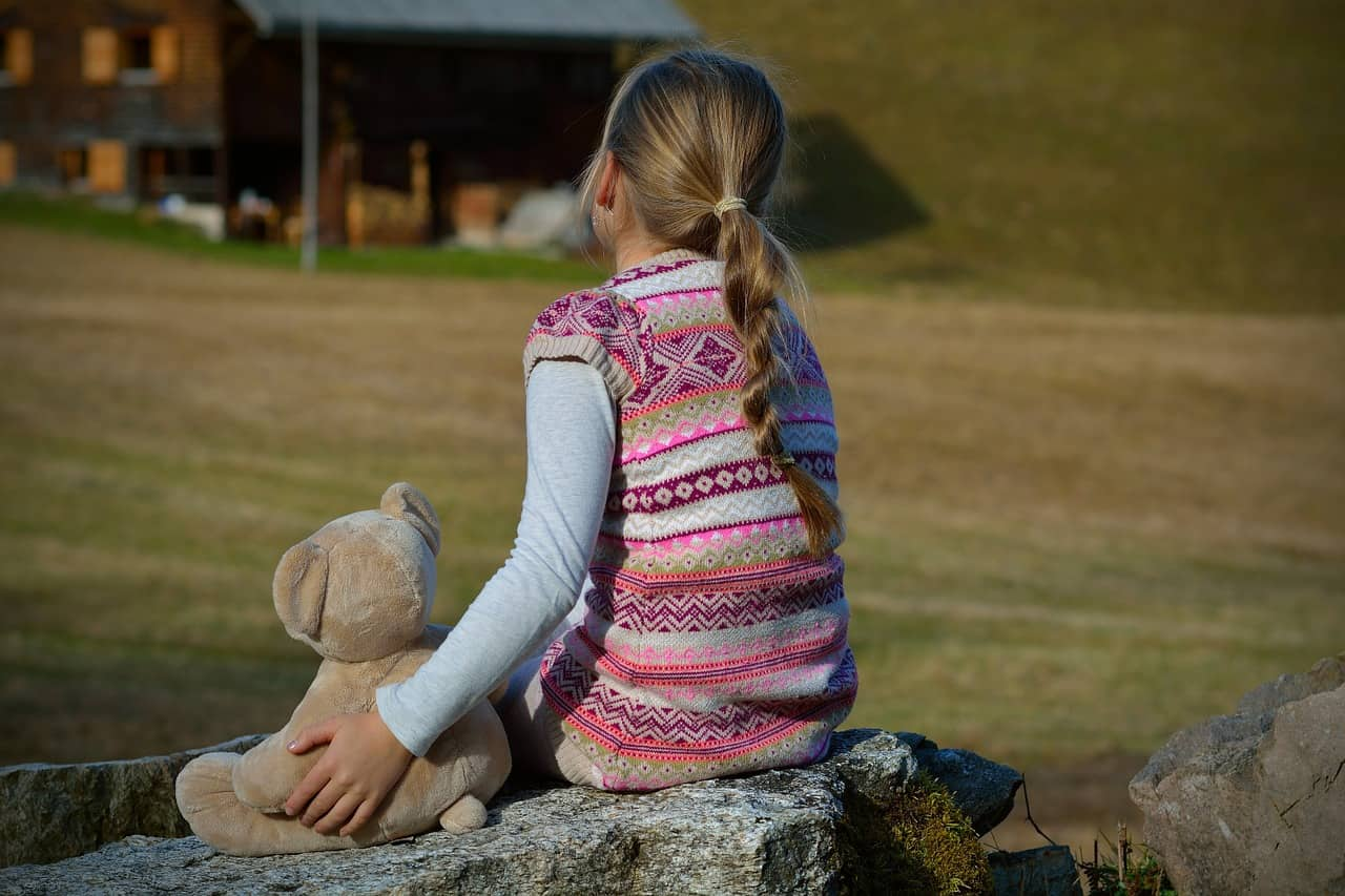 Young girl sitting alone on rock with teddy bear - A is for autism