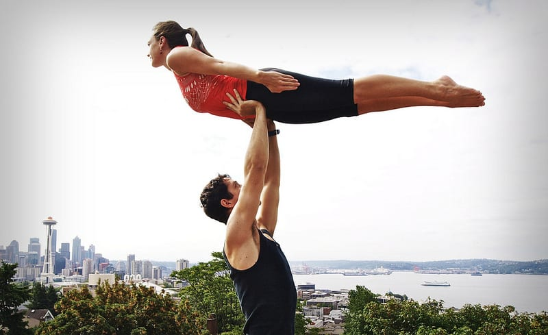 Man lifting woman above head during partner Yoga - The myth of romance