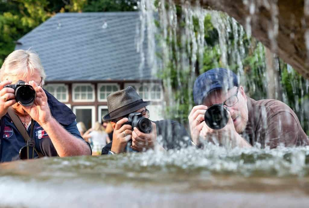 three men with cameras focussing on stream