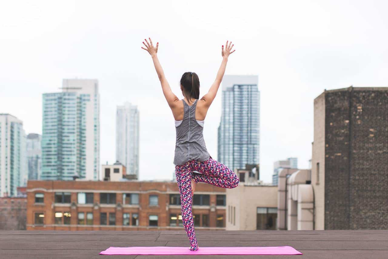 Woman doing tree pose on Yoga mat on roof of building - Lessons from the mat