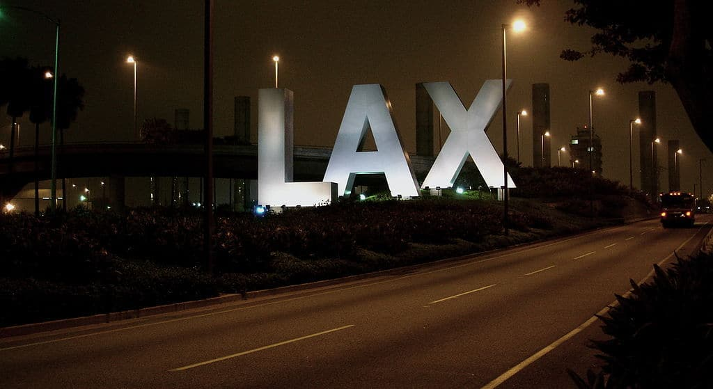 Los Angeles International Airport sign at night - The stories we're living