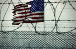 American flag with holes hanging on jail fence - The True American