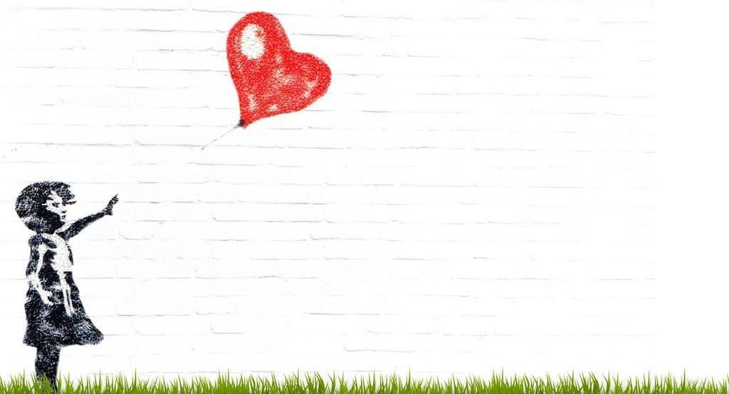 graffiti girl releasing heart balloon