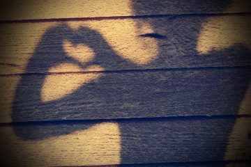 Girl making shadow of heart with hands on wooden wall - Living with intention