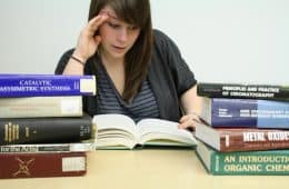 Female student looking skeptically at textbook, while other textbooks surround her - The idiot