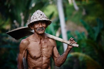 man in the jungle with shovel on shoulderr