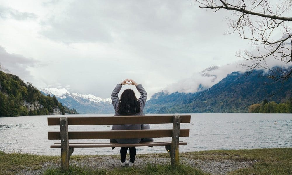 Woman sitting on bench in front of water, stretching arms overhead, making heart with hands - From anxiety to love