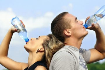Woman and man standing back to back, drinking bottled water - The essential nature of water