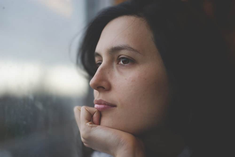Young woman thinking while looking out window - About suicide