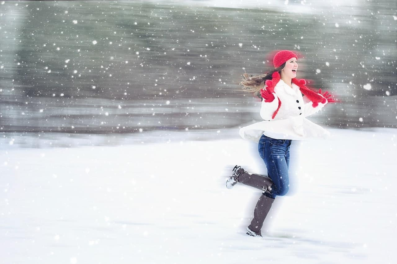 Happy woman running in snow - Find your heart centre