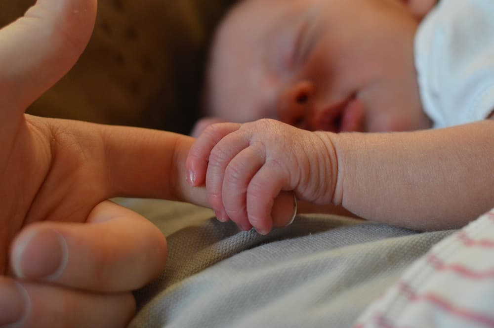 Baby holding onto parent's finger - The perfect mother