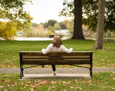Woman sitting on park bench alone - A conversation with sadness