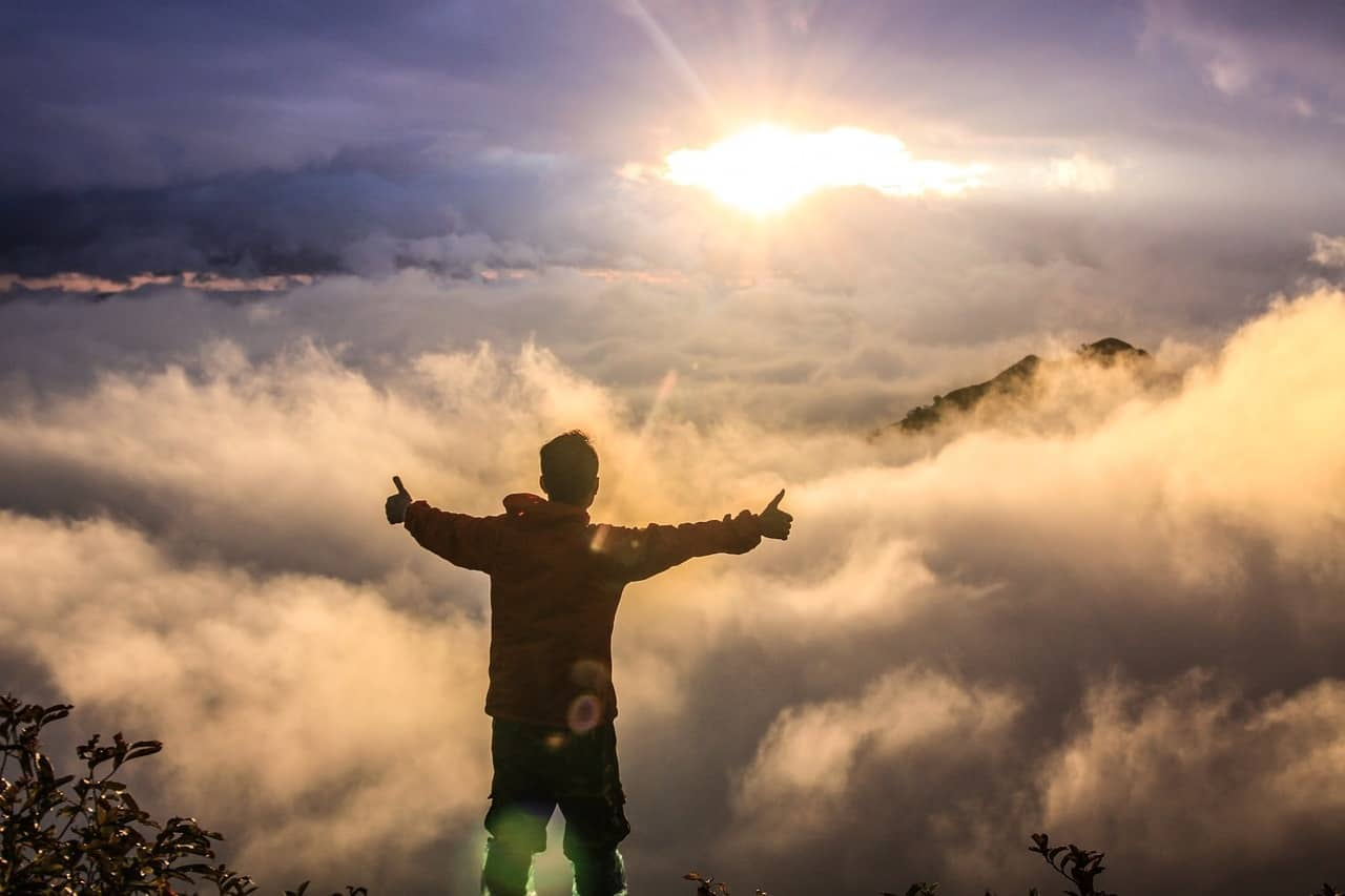 Man on peak looking at clouds with thumbs up - Spiritual energy and the almighty dollar