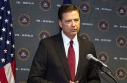 James Comey in front of microphone, beside American flag - A higher loyalty