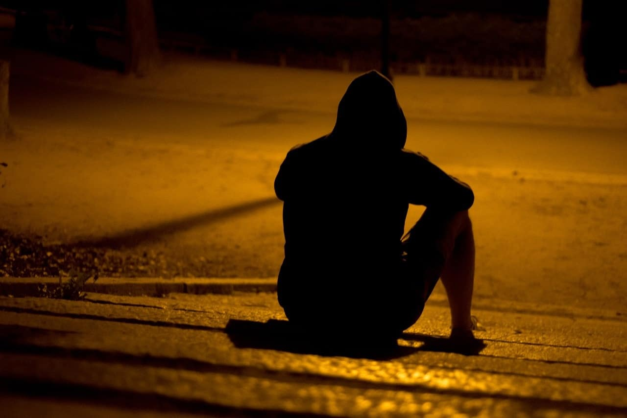 Man sitting alone outdoors in dark with hood on - The ingredients of unhappiness