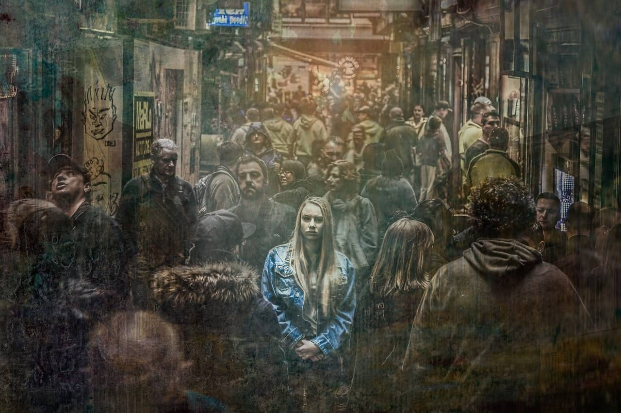 Image of crowd, focusing on unhappy woman in centre - The ingredients of unhappiness