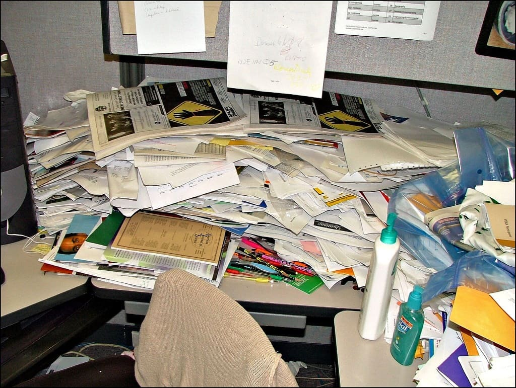 Messy desk covered in paper and other items - The peace within