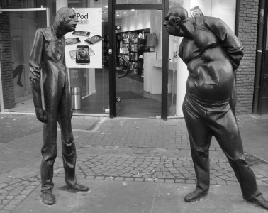 statue of skinny man looking at fat man