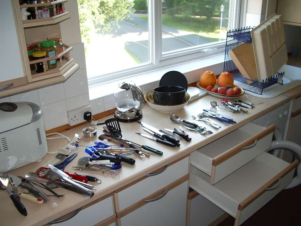 Cleaning out cutlery drawer with cutlery spread out on kitchen counter - Minimalist living
