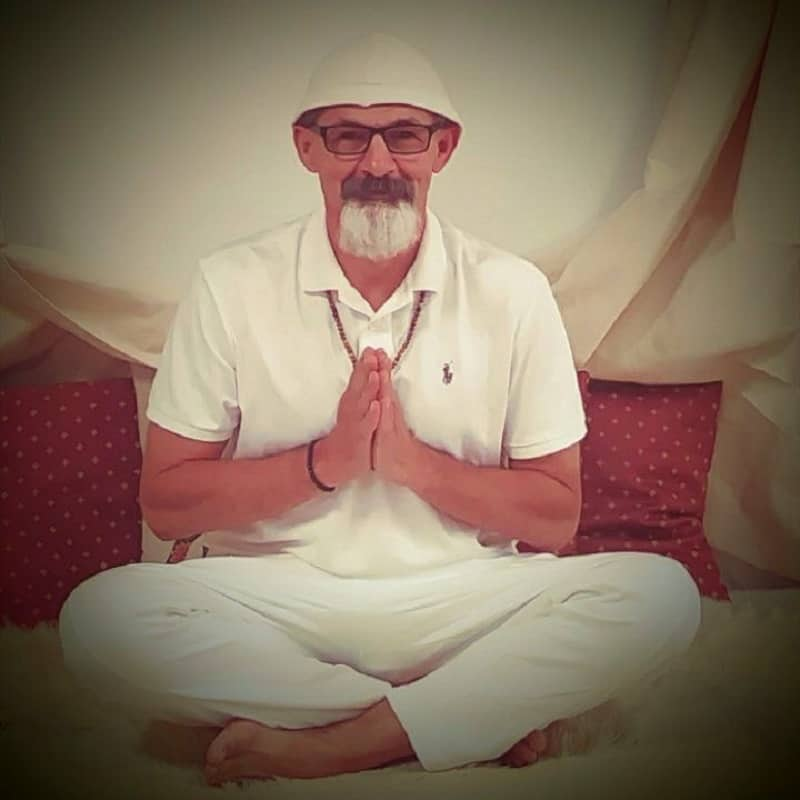 The author sitting alone, cross-legged with hands in prayer position - A course in self-mastery