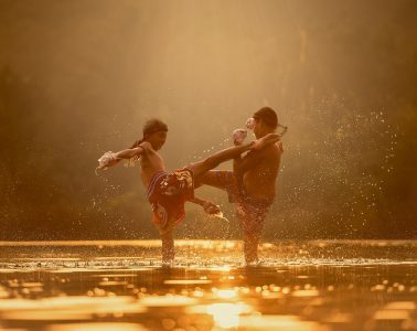 two young boys kickboxing in a river