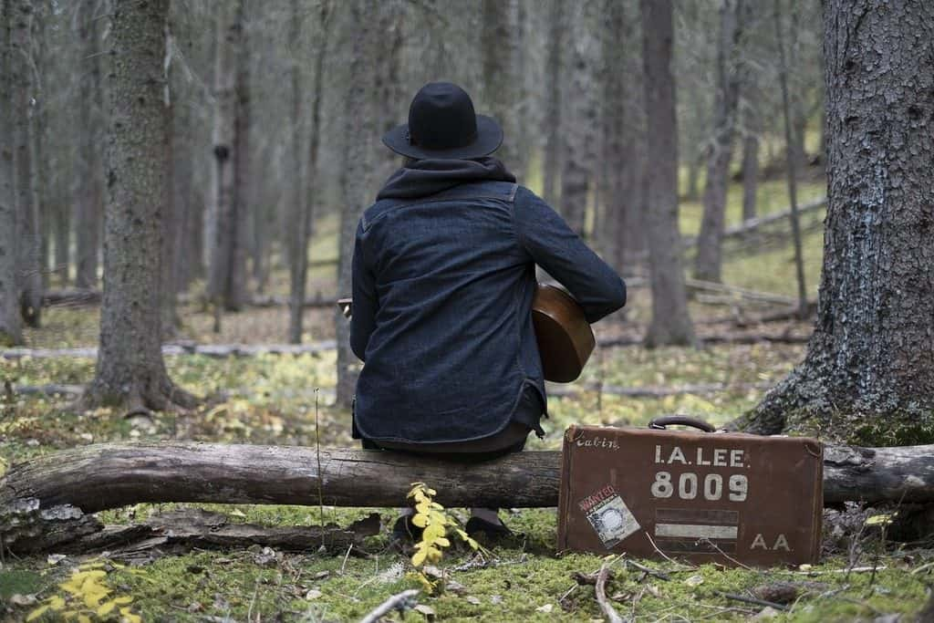 guy sitting on a log playing guitar