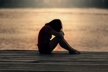 Sad young woman sitting on dock at sunset - Life lessons from a broken heart