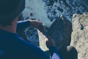 Male hiker on top of mountains with map - What is freedom