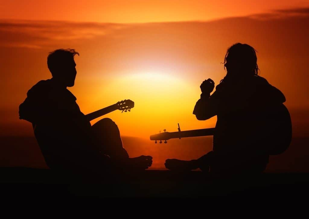 two people playing guitars at sunset