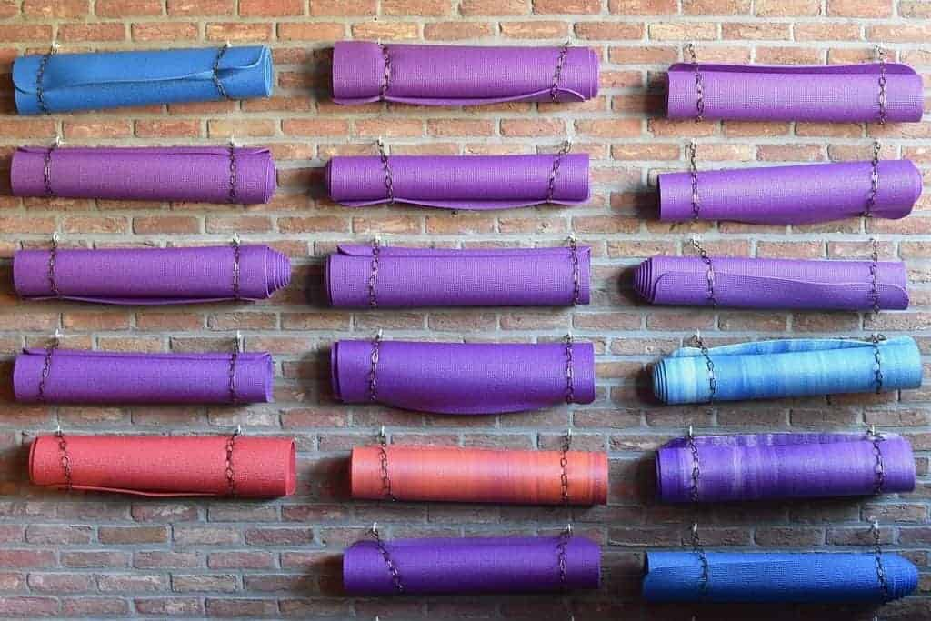 rolled yoga mats on a wall