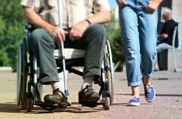 Woman walking with man in wheelchair - Lonely no more