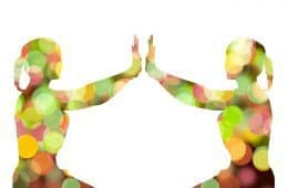 Two colored female silhouettes facing each other, meditating - What is reality?