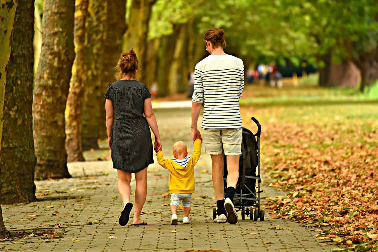 Parents walking with toddler and baby carriage in autumn - Calm down and feel joyful