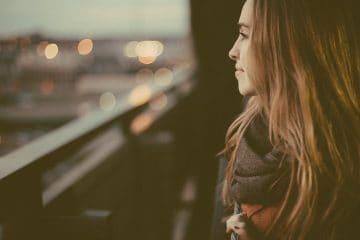 Peaceful woman looking over balcony - Keep calm and feel joyful