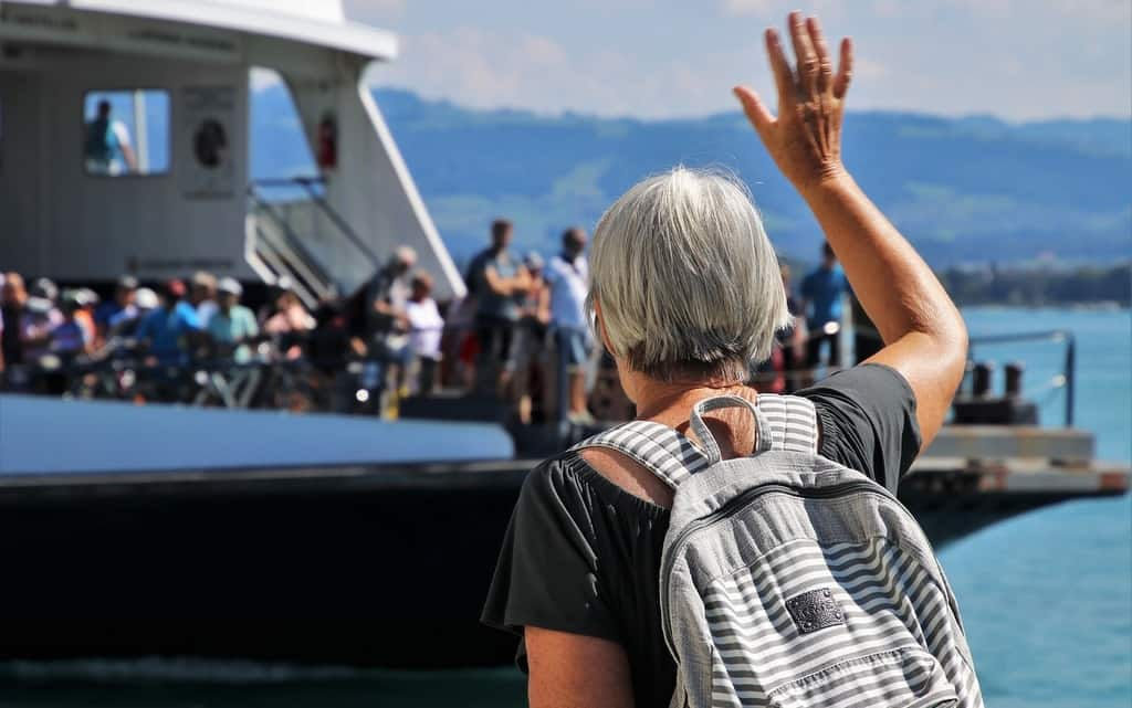 woman waving at seniors on a cruise shi[