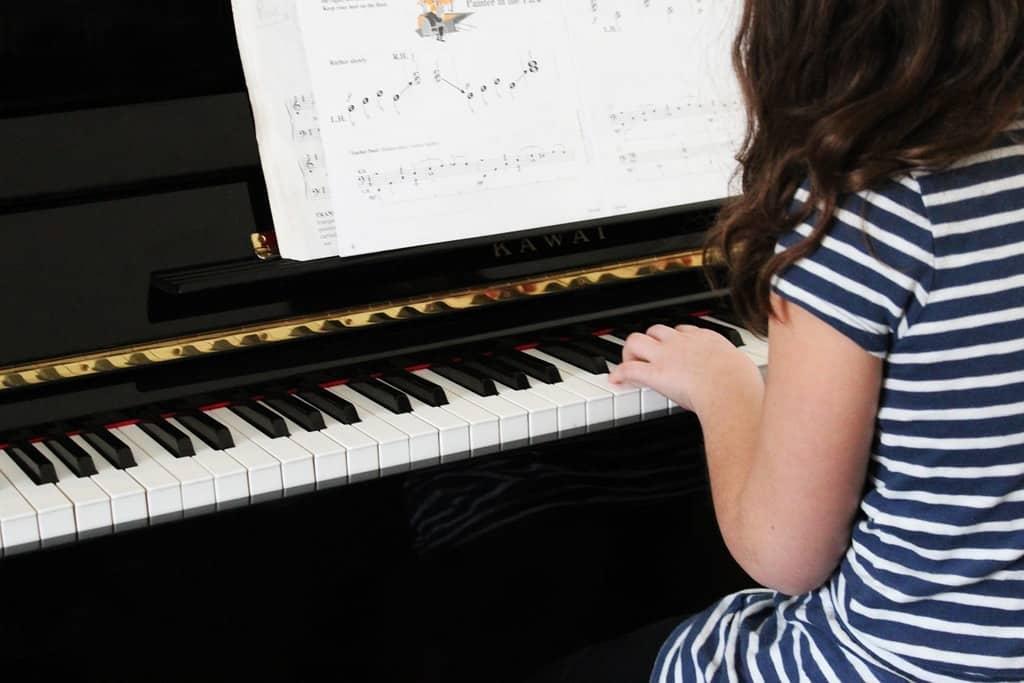 child practising piano