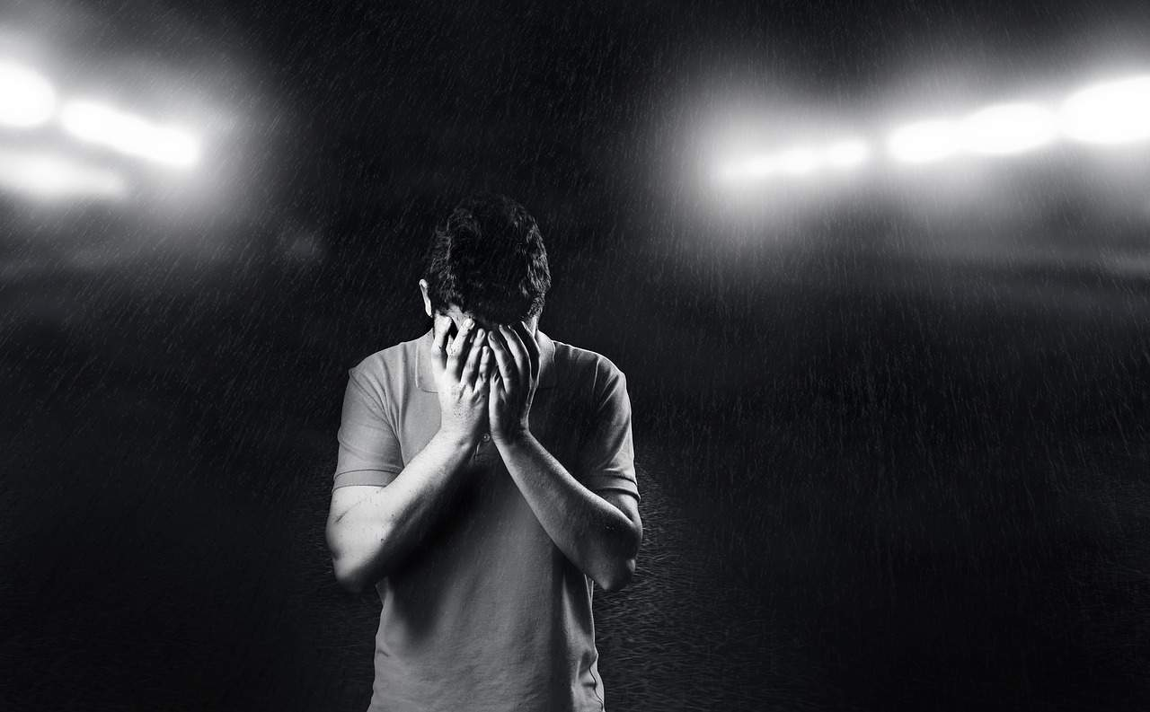 Sad man with hands over face in rain - Blessed