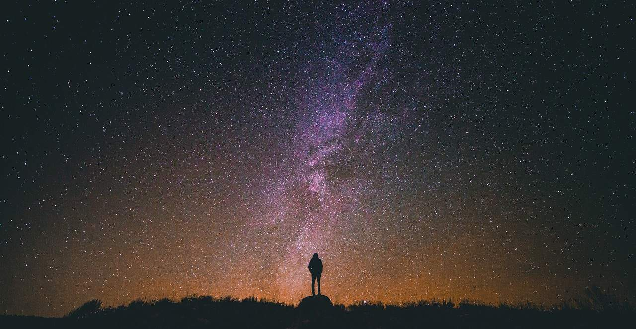 Small silhouette of person standing underneath vast starry sky - Blessed