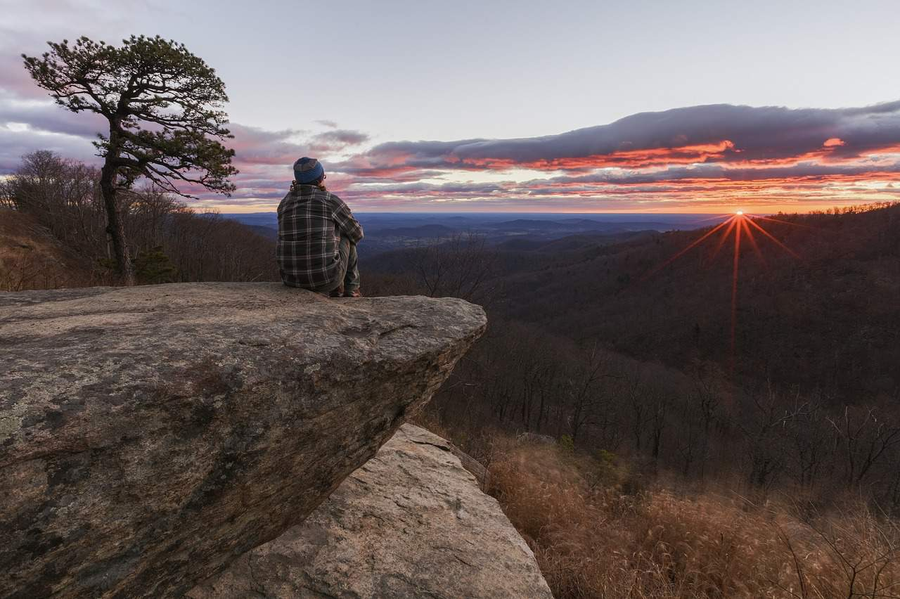Person sitting on rock at sunrise - Forgiveness made easy